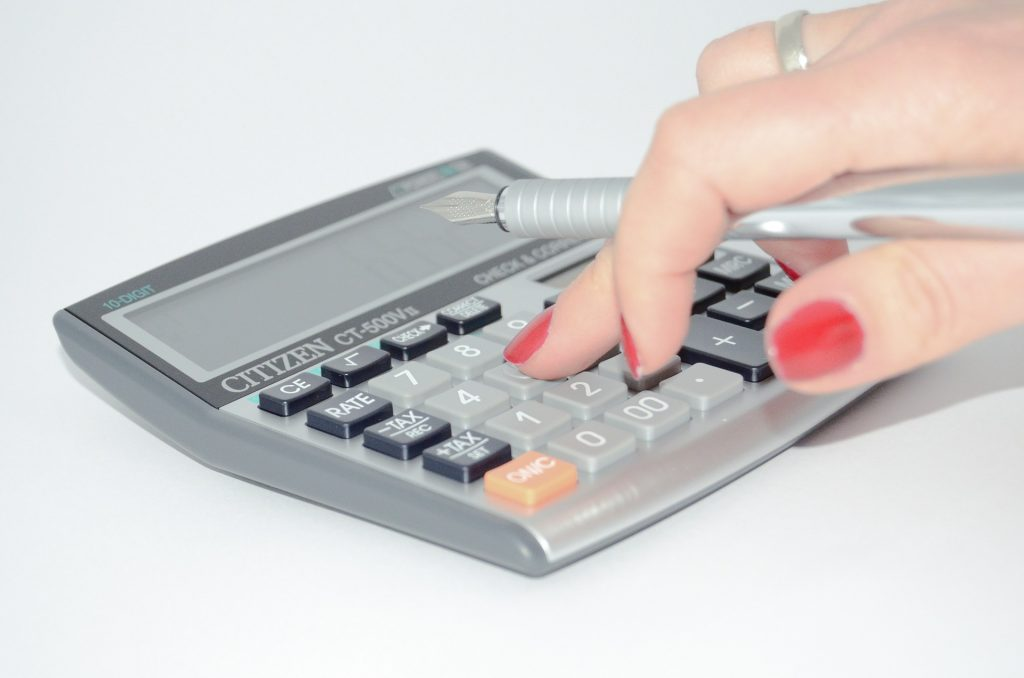 a woman's hand with red nails holding a pen on top of the calculator