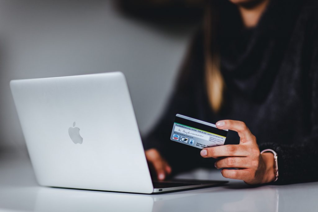 a woman with a credit card using the laptop